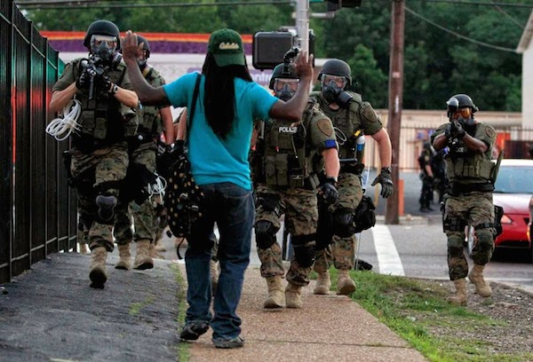 Riot police walk toward a man with his hands raised in Ferguson, Mo. (Jeff Roberson—AP)