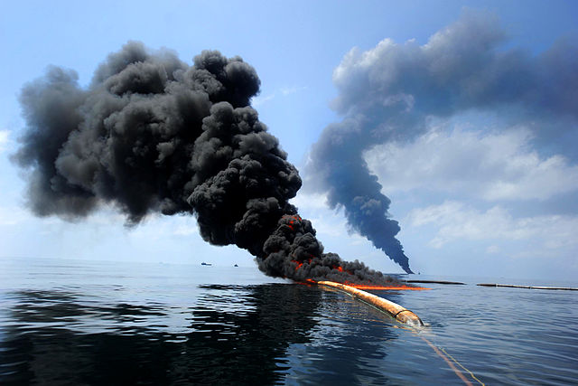 Dark clouds of smoke and fire emerge as oil burns during a controlled fire in the Gulf of Mexico, May 6, 2010. The U.S. Coast Guard, working with BP, local residents and other federal agencies, conducted the burn to help prevent the spread of oil following the explosion on Deepwater Horizon, an offshore drilling unit. (Credit: US Navy via Wikimedia)
