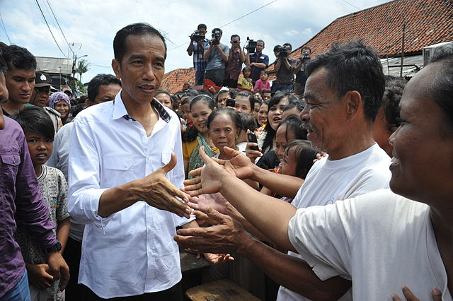 President Jokowi, then Governor of Jakarta, shakes hands with a crowd in January 2013. (Credit: Provincial Government of Jakarta via Wikimedia)
